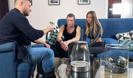 Парень сидя на кресле, смотрит как его русская подружка изме...